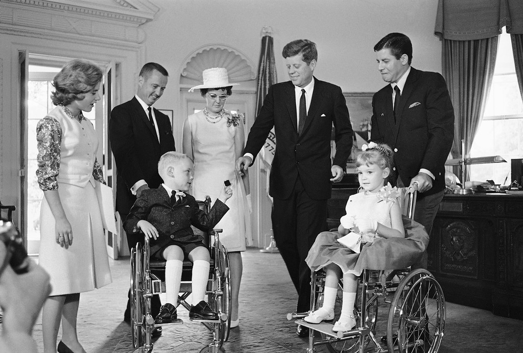 . President John Kennedy reaches for a gift from Bobbie Whittaker, 7,  in his White House office in Washington, June 20, 1963.          Bobbie and his six-year-old sister, Kerrie, right, are the new national poster children of the Muscular Dystrophy Association. Standing, from left, are actress Patty Duke; the children\'s parents, Mr. and Mrs. C. Leigh Whittaker of Cincinnati; Kennedy and comedian Jerry Lewis.     Kennedy received a lapel pin from Bobby, flowers from Kerrie.    (AP Photo/John Rous)