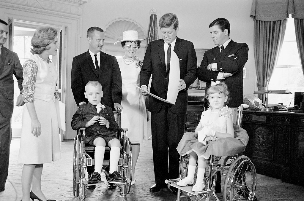. President John Kennedy looks at  a gift from Bobbie Whittaker, 7,  in his White House office in Washington, June 20, 1963.  Bobbie and his six-year-old sister, Kerrie, right, are the new national poster children of the Muscular Dystrophy Association. Standing, from left, are actress Patty Duke; the children\'s parents, Mr. and Mrs. C. Leigh Whittaker of Cincinnati; Kennedy and comedian Jerry Lewis.  Kennedy received a lapel pin from Bobby, flowers from Kerrie.    (AP Photo/John Rous)