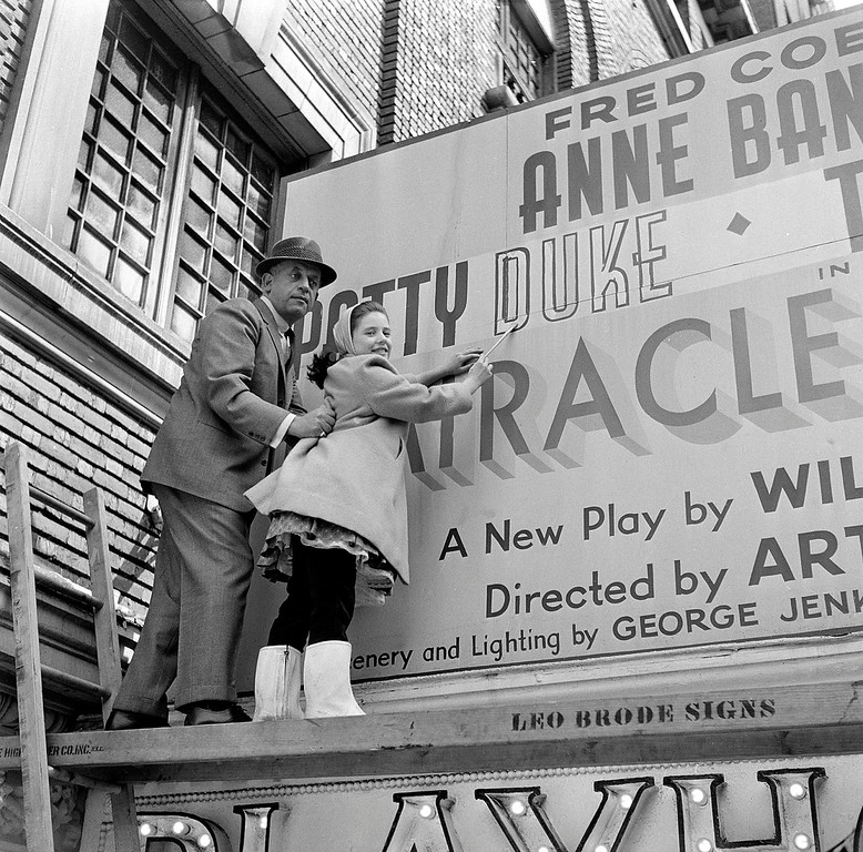 ". Child actress Patty Duke is filling out the letters of her name as it appears on the marquee at the Playhouse Theatre in New York City, advertising the play ""The Miracle Worker,\"" on March 25, 1960. 13-year-old Patty, who stars opposite Anne Bancroft in the hit show, is held and supported by Mannie Kay, president of the sign company. Duke, who won an Oscar as a child at the start of an acting career that continued through her adulthood, died Tuesday, March 29, 2016, of sepsis from a ruptured intestine. She was 69. (AP Photo)"
