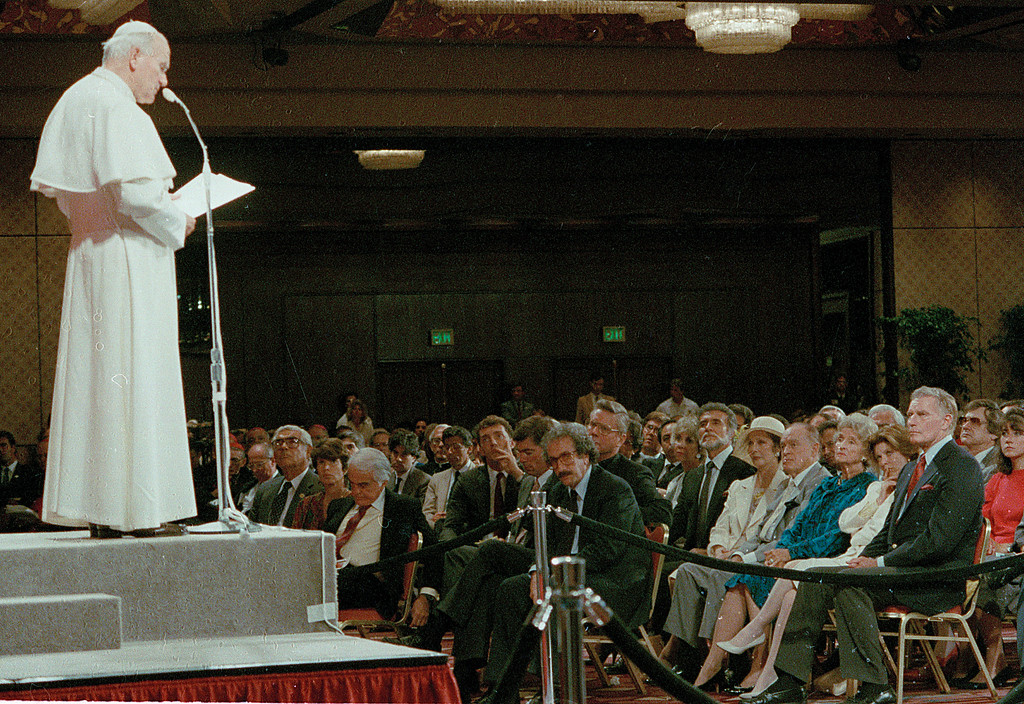 . Pope John Paul II talks with the media and entertainment industry professionals at the Registry hotel in Los Angeles, Calif., Tuesday afternoon, Sept. 15, 1987.  Seated in the audience at the bottom right from front to back are, Charlton Heston, Patty Duke, Delores Hope, Bob Hope, Loretta Young and Ricardo Montalban, with beard.  In the front row, looking down, is Jack Valenti.  (AP Photo/David M. Tenenbam)