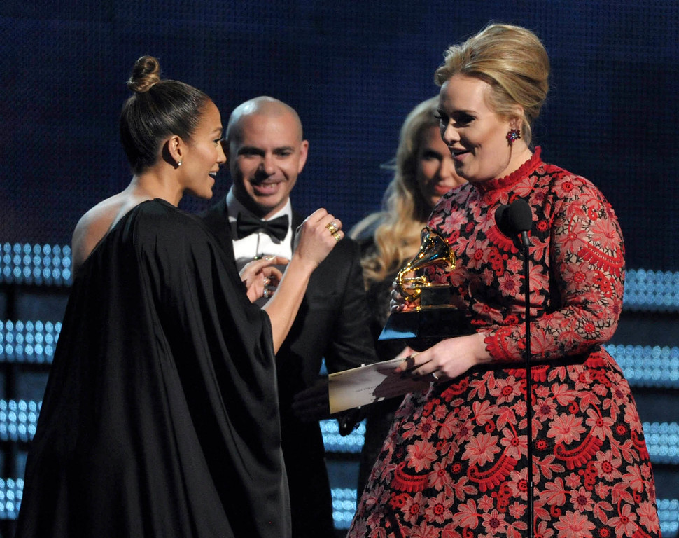 ". Singer and actress Jennifer Lopez, left, and recording artist Pitbull present the award for best pop solo performance for ""Set Fire to the Rain\"" to Adele, right, at the 55th annual Grammy Awards on Sunday, Feb. 10, 2013, in Los Angeles. (Photo by John Shearer/Invision/AP)"