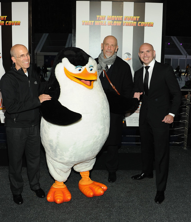 ". NEW YORK, NY - NOVEMBER 16:  (L-R) CEO of DreamWorks Animation Jeffrey Katzenberg, actor John Malkovich and rapper Pitbull attend ""Penguins Of Madagascar\"" New York premiere at Winter Village at Bryant Park Ice Rink on November 16, 2014 in New York City.  (Photo by Andrew Toth/Getty Images)"