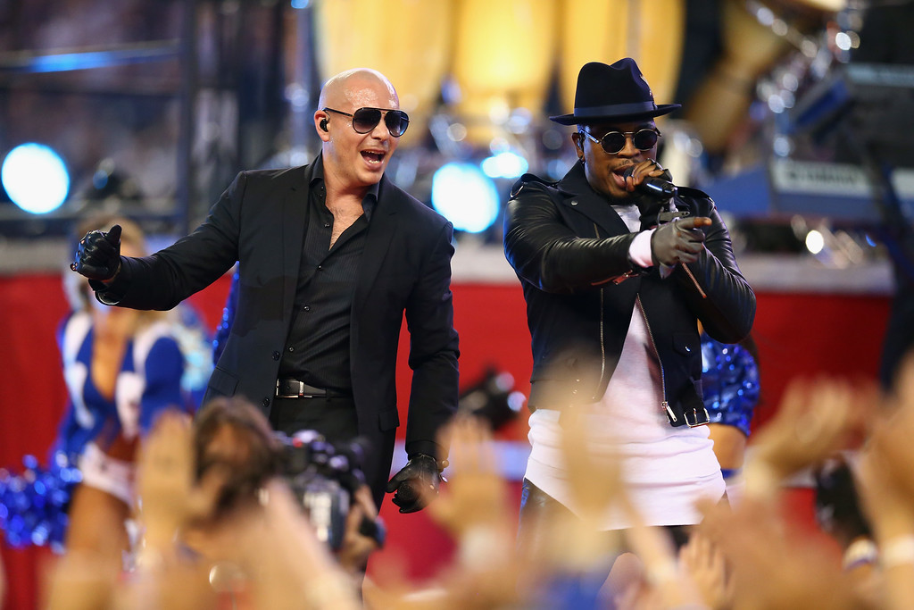 . ARLINGTON, TX - NOVEMBER 27:  Singer Pitbull and Ne-Yo performs during halftime of the Thanksgiving Day game between the Philadelphia Eagles and the Dallas Cowboys in the first half at AT&T Stadium on November 27, 2014 in Arlington, Texas.  (Photo by Ronald Martinez/Getty Images)