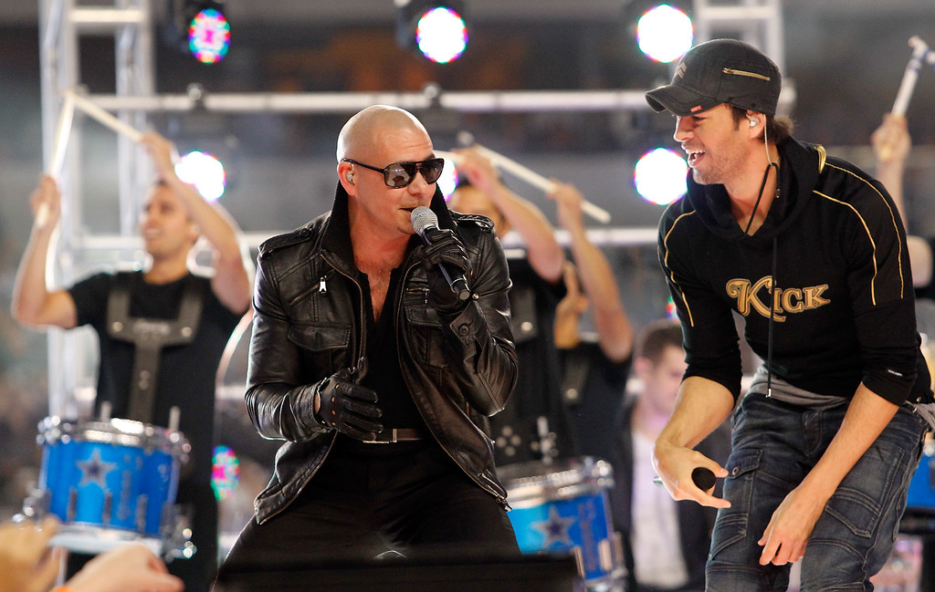 . ARLINGTON, TX - NOVEMBER 24:  Singers Pitbull (L) and Enrique Iglesias (R) perform at halftime during the Thanksgiving Day game between the Miami Dolphins and the Dallas Cowboys at Cowboys Stadium on November 24, 2011 in Arlington, Texas.  (Photo by Tom Pennington/Getty Images)