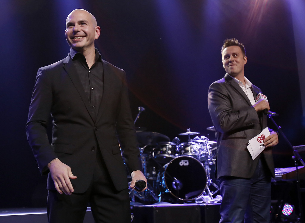 . BURBANK, CA - NOVEMBER 19:  Pitbull (L) speaks to DJ Jesse Lazano on the Honda Stage at the iHeartRadio Theater Los Angeles on November 19, 2014 in Burbank, California.  (Photo by Mike Windle/Getty Images for iHeartMedia)