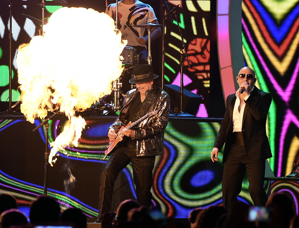 . LAS VEGAS, NV - NOVEMBER 20:  Recording artists Carlos Santana (L) and Pitbull perform during the 15th annual Latin GRAMMY Awards at the MGM Grand Garden Arena on November 20, 2014 in Las Vegas, Nevada.  (Photo by Ethan Miller/Getty Images)