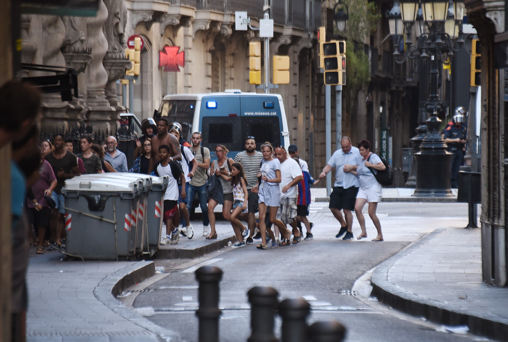 . People flee from the scene after a white van jumped the sidewalk in the historic Las Ramblas district of Barcelona, Spain, crashing into a summer crowd of residents and tourists Thursday, Aug. 17, 2017.   According to witnesses the white van swerved from side to side as it plowed into tourists and residents. (AP Photo/Giannis Papanikos)