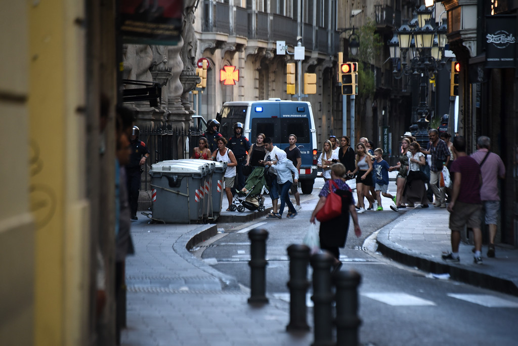 . People flee the scene in Barcelona, Spain, Thursday, Aug. 17, 2017, as police officers patrols after a white van jumped the sidewalk in the historic Las Ramblas district, crashing into a summer crowd of residents and tourists and injuring several people, police said. (AP Photo/Giannis Papanikos)