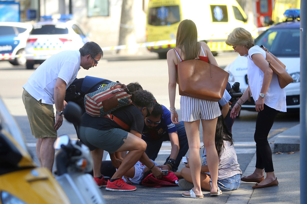 . A person is treated in Barcelona, Spain, Thursday, Aug. 17, 2017 after a white van jumped the sidewalk in the historic Las Ramblas district, crashing into a summer crowd of residents and tourists and injuring several people, police said. (AP Photo/Oriol Duran)