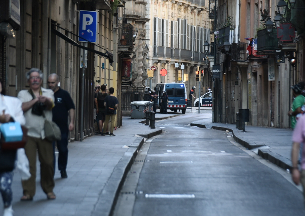 . People flee the scene in Barcelona, Spain, Thursday, Aug. 17, 2017, as police officers patrol after a white van jumped the sidewalk in the historic Las Ramblas district, crashing into a summer crowd of residents and tourists and injuring several people, police said. (AP Photo/Giannis Papanikos)