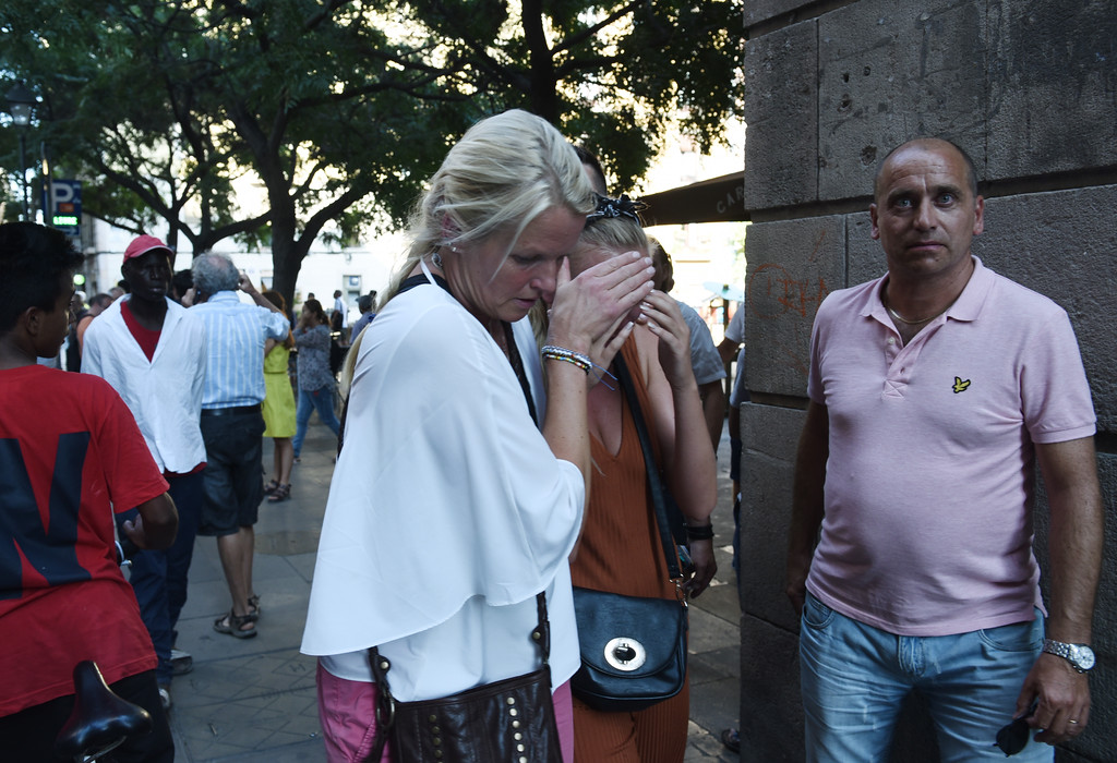 . A woman is comforted as crowds flee from the scene after a white van jumped the sidewalk in the historic Las Ramblas district of Barcelona, Spain, crashing into a summer crowd of residents and tourists Thursday, Aug. 17, 2017.   According to witnesses the white van swerved from side to side as it plowed into tourists and residents. (AP Photo/Giannis Papanikos)