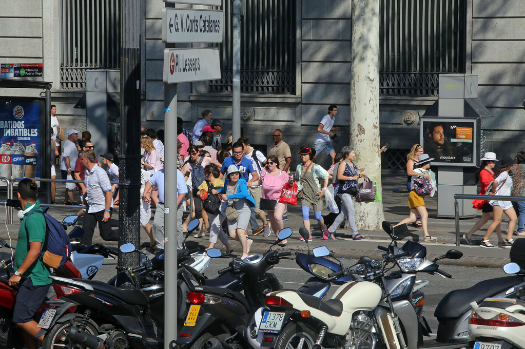 . People flee the scene in Barcelona, Spain, Thursday, Aug. 17, 2017 after a white van jumped the sidewalk in the historic Las Ramblas district, crashing into a summer crowd of residents and tourists and injuring several people, police said. (AP Photo/Oriol Duran)