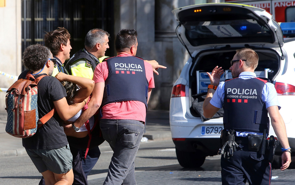 . An injured person is carried in Barcelona, Spain, Thursday, Aug. 17, 2017, after a white van jumped the sidewalk in the historic Las Ramblas district, crashing into a summer crowd of residents and tourists and injuring several people, police said. (AP Photo/Oriol Duran)