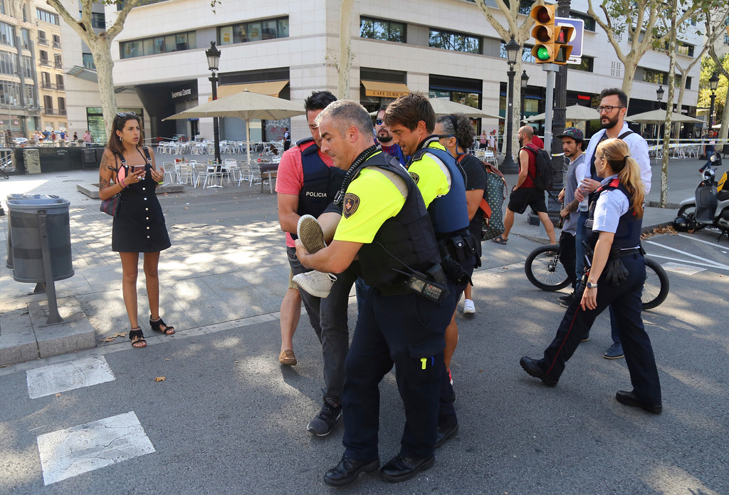 . A person is carried in Barcelona, Spain, Thursday, Aug. 17, 2017 after a white van jumped the sidewalk in the historic Las Ramblas district, crashing into a summer crowd of residents and tourists and injuring several people, police said. (AP Photo/Oriol Duran)