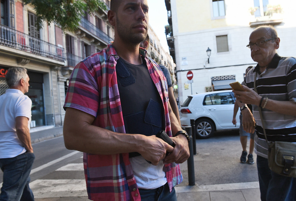 . A plain clothed police officer secures the area in Barcelona, Spain, Thursday, Aug. 17, 2017 after a white van jumped the sidewalk in the historic Las Ramblas district, crashing into a summer crowd of residents and tourists and injuring several people, police said. (AP Photo/Giannis Papanikos)