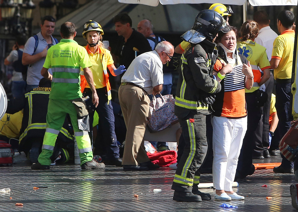 . Injured people are treated in Barcelona, Spain, Thursday, Aug. 17, 2017 after a white van jumped the sidewalk in the historic Las Ramblas district, crashing into a summer crowd of residents and tourists and injuring several people, police said. (AP Photo/Oriol Duran)