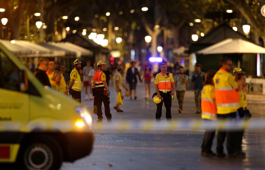 . Emergency workers stand on a blocked street in Barcelona, Spain, Thursday, Aug. 17, 2017. A white van jumped up onto a sidewalk and sped down a pedestrian zone Thursday in Barcelona\'s historic Las Ramblas district, swerving from side to side as it plowed into tourists and residents. Police said 13 people were killed and more than 50 wounded in what they called a terror attack. (AP Photo/Manu Fernandez)