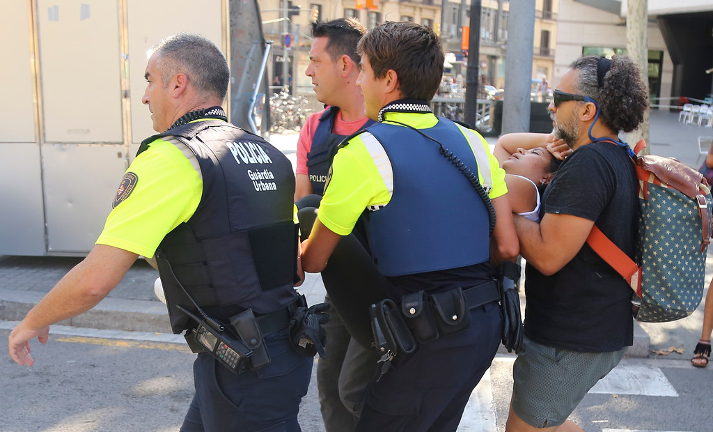 . A woman is carried in Barcelona, Spain, Thursday, Aug. 17, 2017 after a white van jumped the sidewalk in the historic Las Ramblas district, crashing into a summer crowd of residents and tourists and injuring several people, police said. (AP Photo/Oriol Duran)