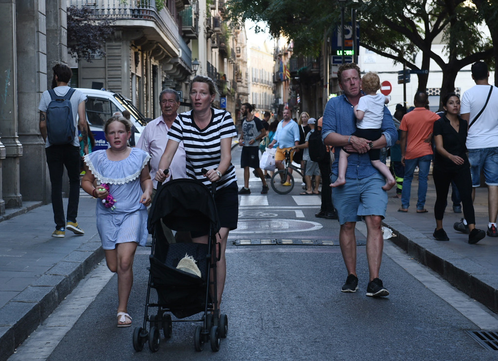 . People flee the scene in Barcelona, Spain, Thursday, Aug. 17, 2017 after a white van jumped the sidewalk in the historic Las Ramblas district, crashing into a summer crowd of residents and tourists and injuring several people, police said. (AP Photo/Giannis Papanikos)