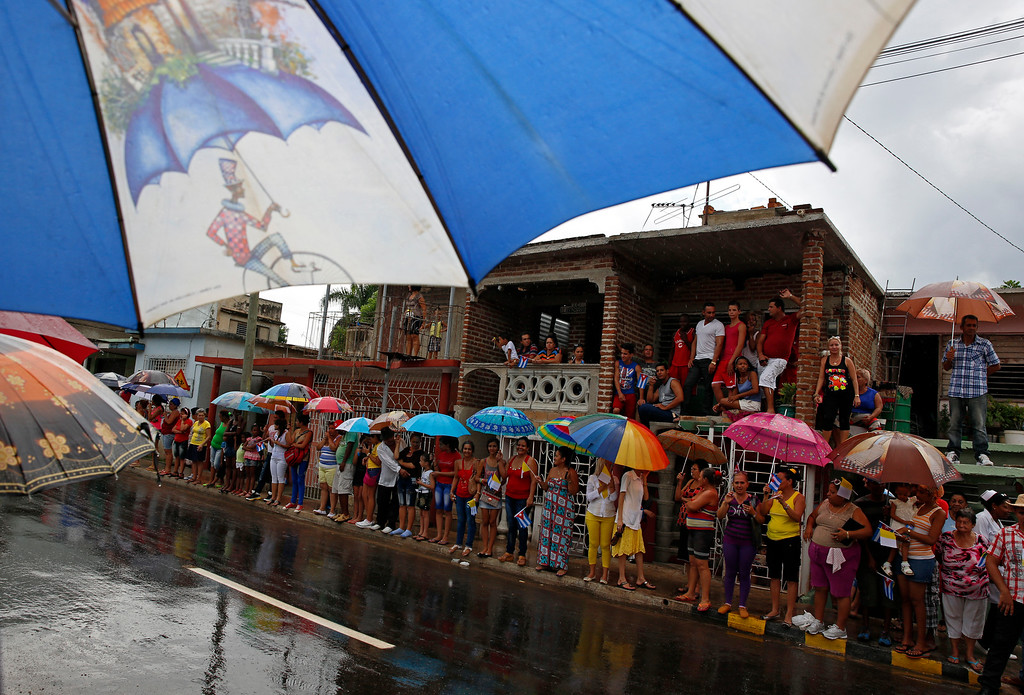 . Residents wait under the rain for Pope\'s Francis aboard his popemobile on the way to the Hill of the Cross in Holguin, Cuba, Monday, Sept. 21, 2015. Francis is ending his time in Holguin by blessing Cuba\'s fourth-largest city from the Hill of the Cross, a pilgrimage site overlooking the city. (AP Photo/Enric Marti)