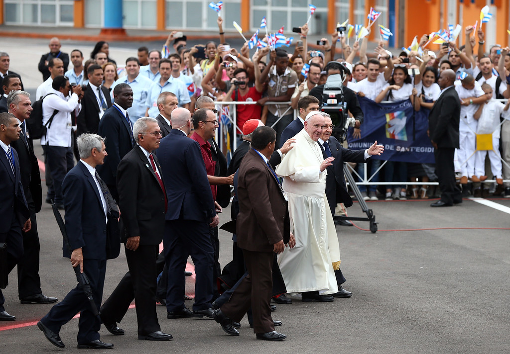 . People wave Cuban and Vatican flags as Pope Francis walks with Cuba\'s President Raul Castro (R) after arriving at Jose Marti International Airport on September 19, 2015 in Havana, Cuba. Pope Francis is at the beginning of a three day visit to Cuba where he will meet President Raul Castro and hold Mass in Revolution Square before travelling to Holguin, Santiago de Cuba and El Cobre then onwards to the United States.  (Photo by Carl Court/Getty Images)