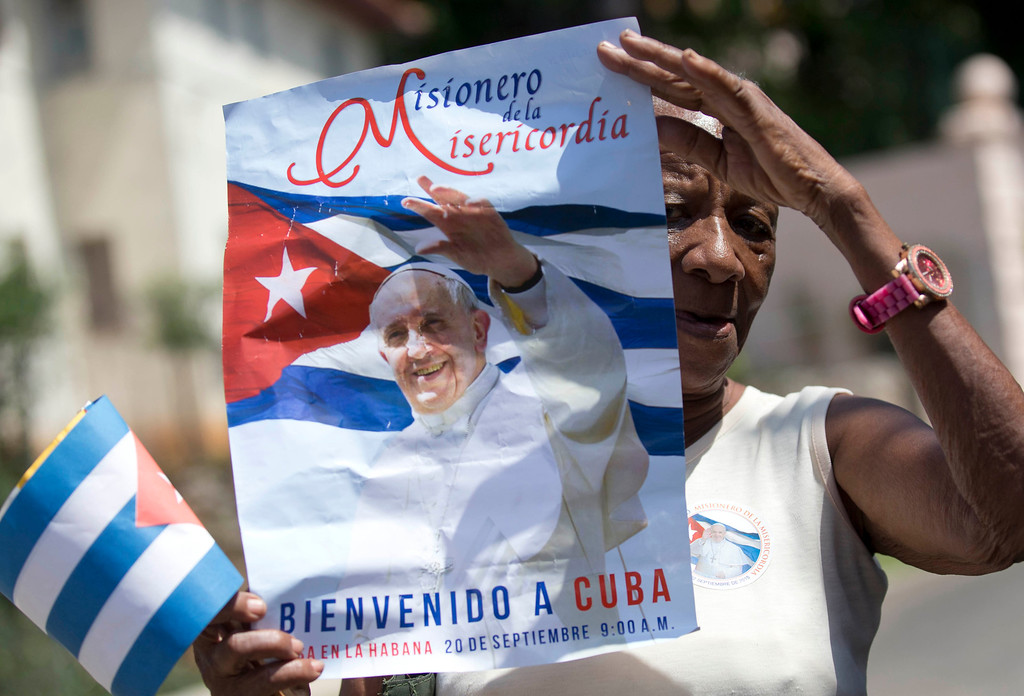 . A woman holds up a banner of Pope Francis as she waits for his arrival outside the Apostolic Nunciature in Havana, Cuba, Saturday, Sept. 19, 2015. Pope Francis begins a 10-day trip to Cuba and the United States on Saturday, embarking on his first trip to the onetime Cold War foes after helping to nudge forward their historic rapprochement.  (AP Photo/Alessandra Tarantino)
