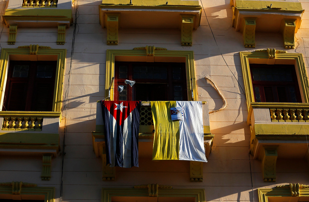. Vatican and Cuban flags hang from a balcony in Reina Street before the arrival of Pope Francis in Havana, Cuba, Saturday, Sept. 19, 2015. Pope Francis begins a 10-day trip to Cuba and the United States on Saturday, embarking on his first trip to the onetime Cold War foes after helping to nudge forward their historic rapprochement.(AP Photo/Desmond Boylan)