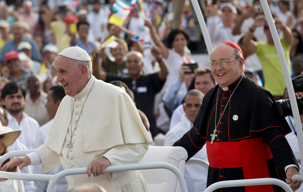 . Cuba\'s Cardinal Jaime Ortega, right, stands behind Pope Francis in the popemobile as they arrive for Mass at Revolution Plaza in Havana, Cuba, Sunday, Sept. 20, 2015. During Mass Sunday, Ortega thanked the pope for his work promoting detente between Havana and Washington and called for reconciliation between Cubans living on the island and elsewhere. Ortega was among many priests sent to military-run agricultural camps in the 1960s after Fidel Castro declared Cuba to be socialist and accused prominent Catholics of trying to topple him. (Ismael Francisco/Cubadebate Via AP)