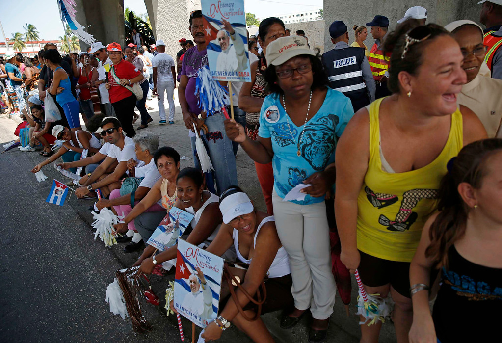 . People wait the arrival of Pope Francis on a road outside the airport in Havana, Cuba, Saturday, Sept. 19, 2015. Fewer than a third of Cubans identify as Catholic, but rural Cubans are speaking warmly of the pope\'s role in mediating detente between the U.S. and Cuba. (AP Photo/Enric Marti)