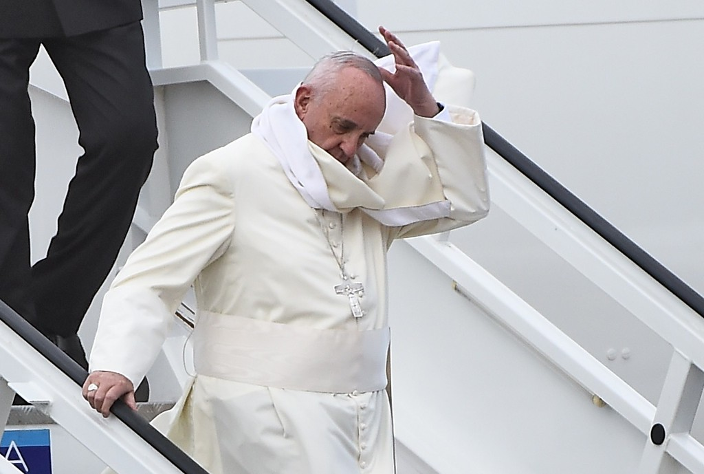 . Pope Francis fails to catch his skull cap after it was blown away by the wind as he descends from the plane upon landing at Havana\'s international airport on September 19, 2015 on the first leg of a high-profile trip that will also take him to the United States. The Alitalia plane carrying Pope Francis touched down at Havana\'s Jose Marti airport at 3:50 pm (1950 GMT), as thousands of people lined the road into the city, which was decked out in giant posters of the Argentine pontiff.          ( FILIPPO MONTEFORTE/AFP/Getty Images)