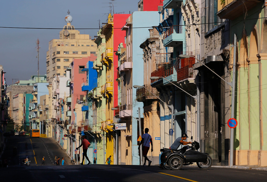 . A man pushes his motorcycle as people walk on the freshly painted Reina Street on the route that Pope Francis will ride on his popemobile in Havana, Cuba, Saturday, Sept. 19, 2015. Pope Francis begins a 10-day trip to Cuba and the United States on Saturday, embarking on his first trip to the onetime Cold War foes after helping to nudge forward their historic rapprochement.(AP Photo/Desmond Boylan)