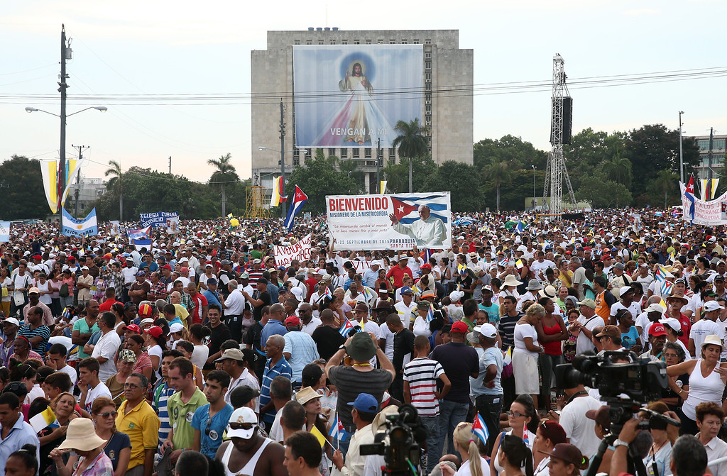 . People look on as Pope Francis performs Mass on September 20, 2015 in Revolution Square in Havana, Cuba. Pope Francis is on the first full day of his three day visit to Cuba where he will meet President Raul Castro and hold Mass in Revolution Square before travelling to Holguin, Santiago de Cuba and El Cobre then onwards to the United States. (Photo by Carl Court/Getty Images)