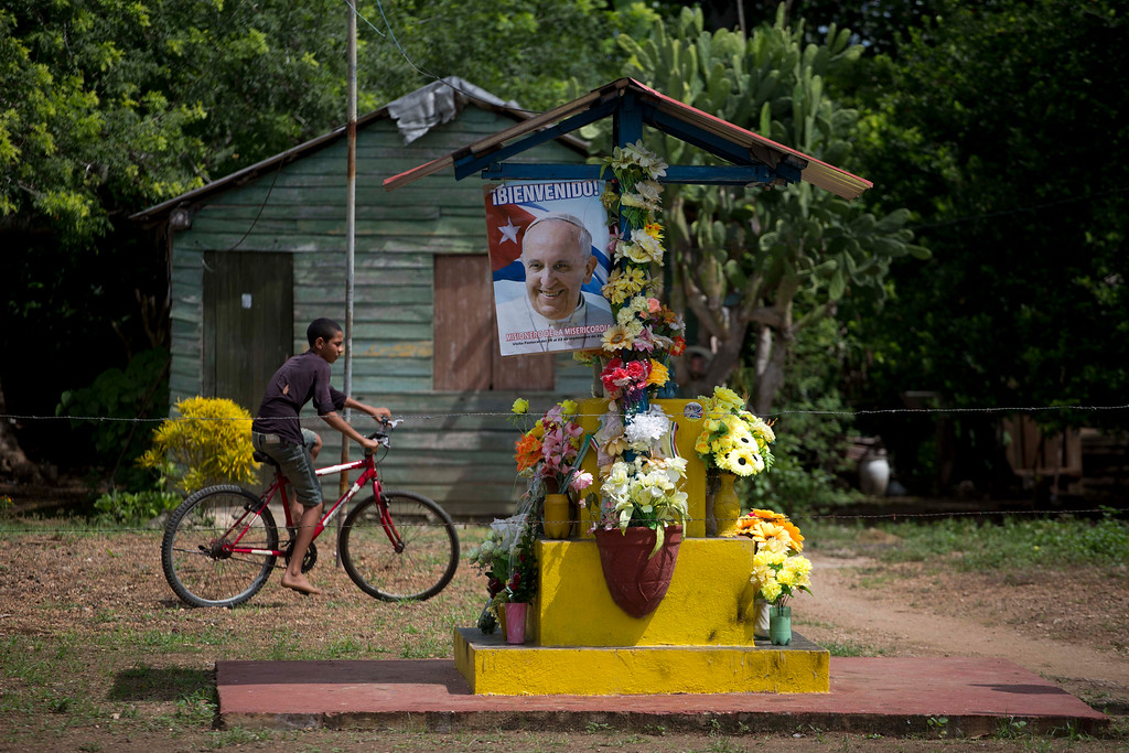 . A child riding his bicycle passes next to  poster of Pope Francis adorning an altar dedicated to the Virgin of Charity of Cobre, on the outskirts of Taguasco, Cuba, Friday, Sept. 18, 2015. Pope Francis will be the third Roman Catholic pontiff to visit Cuba when he arrives on Saturday. His schedule includes a Mass on Tuesday at the sanctuary of the Virgin of Charity of Cobre in far-eastern Cuba. (AP Photo/Eduardo Verdugo)