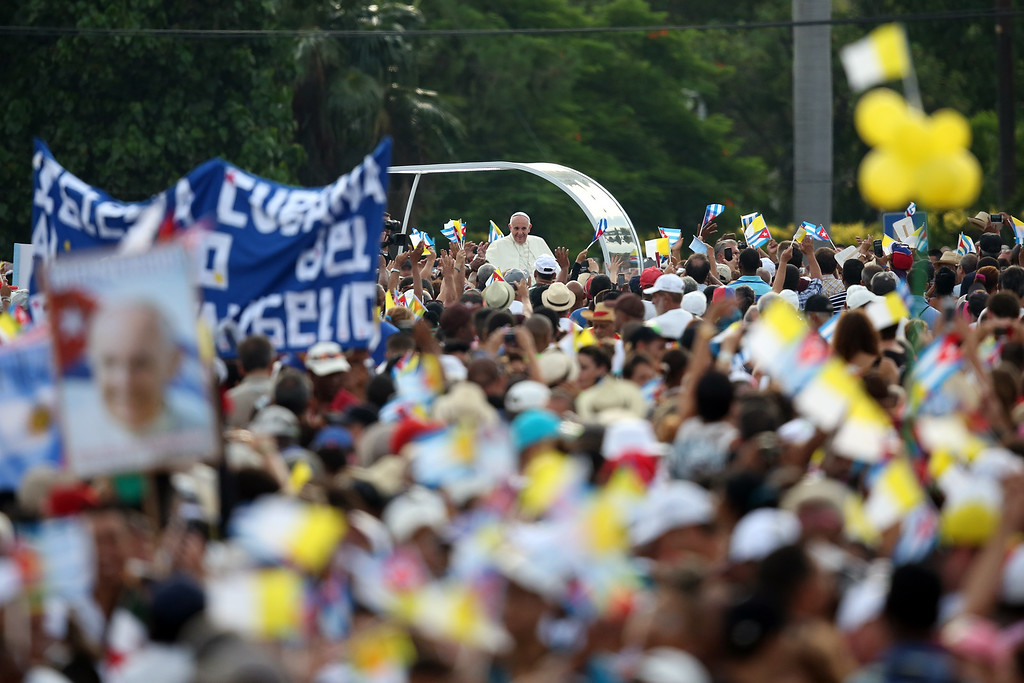 . People wave Cuban and Papal flags as Pope Francis passes by as he arrives to perform Mass on September 20, 2015 in Revolution Square in Havana, Cuba. Pope Francis is on the first full day of his three day visit to Cuba where he will meet President Raul Castro and hold Mass in Revolution Square before travelling to Holguin, Santiago de Cuba and El Cobre then onwards to the United States.  (Photo by Carl Court/Getty Images)