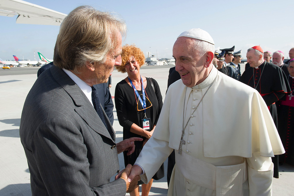 . Pope Francis is greeted by Alitalia CEO and chairman Luca Cordero di Montezemolo as he arrives to board his flight to La Habana, Cuba, where he will start a 10-day trip including the United States, at Rome\'s Fiumicino international airport, Saturday, Sept. 19, 2015. (L\'Osservatore Romano/Pool Photo via AP)