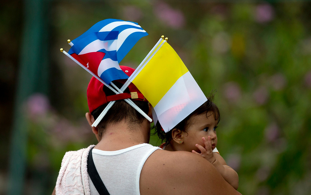 . A man with Cuban and Vatican flags tucked into his hat waits for Pope Francis to arrive at the Apostolic Nunciature in Havana, Cuba, Saturday, Sept. 19, 2015. Pope Francis began his 10-day trip to Cuba and the United States, embarking on his first trip to the onetime Cold War foes after helping to nudge forward their historic rapprochement. (AP Photo/Alessandra Tarantino)