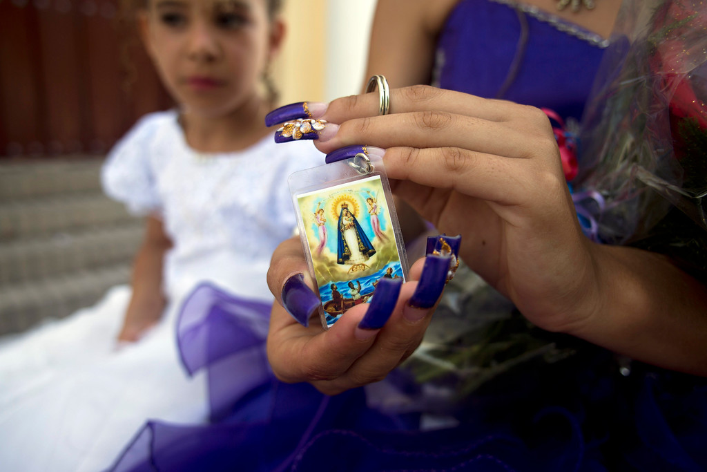". Yelenis Teruel Salas shows her image of the Virgin of Charity outside the San Isidoro Cathedral where she prayed as part of her 15th birthday celebrations, or ""quinceañera\"" in Holguin, Cuba, Saturday, Sept. 19, 2015, on the day Pope Francis arrives to Cuba. Fewer than a third of Cubans identify as Catholic, but rural Cubans are speaking warmly of the pope\'s role in mediating detente between the U.S. and Cuba. (AP Photo/Eduardo Verdugo)"