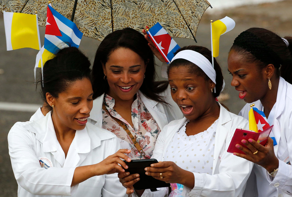 . Medical staff from a nearby hospital, wearing Vatican and Cuban flags in their hair, look at pictures on their mobile phone while waiting for Pope Francis\' motorcade in Havana, Cuba, Saturday, Sept. 19, 2015. Pope Francis began his 10-day trip to Cuba and the United States, embarking on his first trip to the onetime Cold War foes after helping to nudge forward their historic rapprochement. (AP Photo/Desmond Boylan)