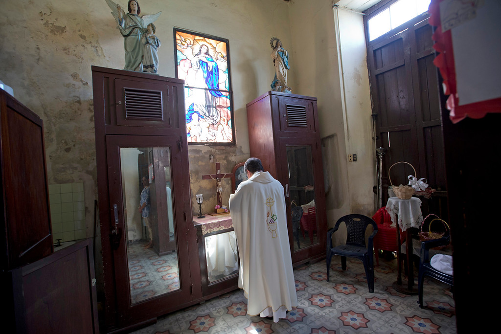 . Father Francisco Garcia prepares before giving Mass at the Jesus del Monte Church in Havana, Cuba Saturday Sept. 19, 2015. Pope Francis begins a 10-day trip to Cuba and the United States on Saturday, embarking on his first trip to the onetime Cold War foes after helping to nudge forward their historic rapprochement. (AP Photo/Alessandra Tarantino)