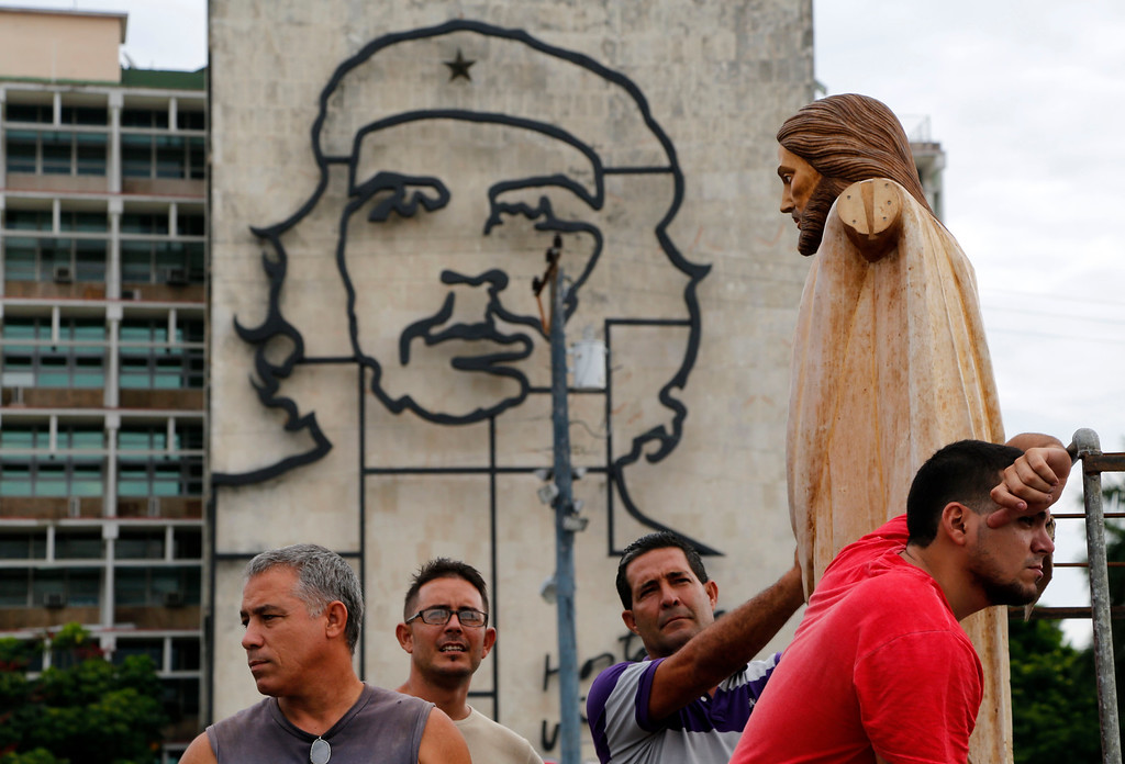 . Backdropped by an iron sculpture of Cuban revolutionary hero Ernesto \'Che\' Guevara on the facade of the Ministry of Interior, workers wait to unload a statue of Christ during preparations of the altar where Pope Francis will deliver a Mass in the Plaza of the Revolution, in Havana, Cuba, Thursday, Sept. 17, 2015. When Francis arrives in Havana on Sept. 19, he\'ll find his church ministering to more Cubans than at any time since the 1959 revolution that brought Fidel Castro to power. (AP Photo/Desmond Boylan)