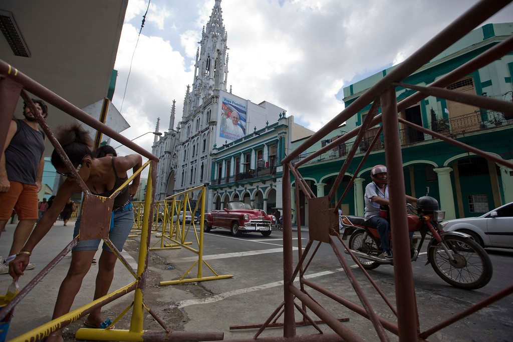. Painters put the last touches on portable street barriers in Havana, Cuba, Friday, Sept. 18, 2015, where a church carries a photo of Pope Francis one day before his arrival. Francis has a close relationship with Cardinal Jaime Ortega, the archbishop of Havana who has overseen the church\'s relationship with the Cuban state since 1981.  (AP Photo/Alessandra Tarantino)