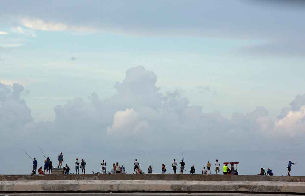 . People fish along the Malecon, the sea wall that runs along the Havana coastline, in Cuba, Friday, Sept. 18, 2015, on the eve of Pope Francis\' visit. Papal observers say it\'s likely Francis will speak strongly to Cubans about the need for greater freedom in their country and may speak to President Raul Castro in private about the same topic. (AP Photo/Alessandra Tarantino)
