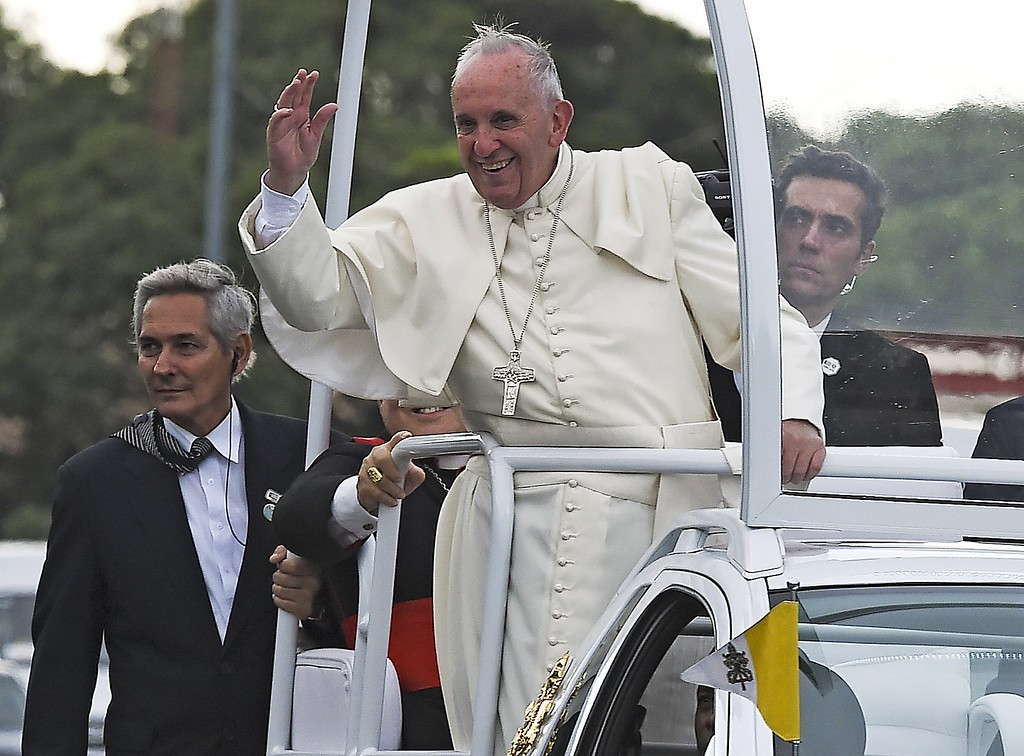 . Pope Francis waves from the Popemobile as he is driven from Jose Marti international airport to Havana\'s downtown during his visit on September 19, 2015. Pope Francis on Saturday urged the United States and Cuba to pursue their nascent reconciliation as he arrived in Havana on the first leg of a high-profile trip that will also take him to the US.         (LUIS ACOSTA/AFP/Getty Images)