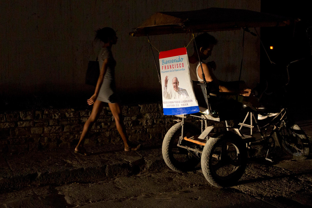 . A poster featuring Pope Francis and a welcome message decorates the back of a tricycle taxi in Havana, Cuba, Friday, Sept. 18, 2015. Francis will visit Cuba from Sept. 19-22, before arriving in the United States, making him the third pontiff to visit the island nation. (AP Photo/Alessandra Tarantino)