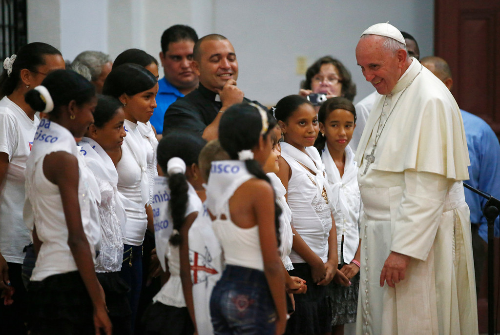 . Pope Francis talks with a group of children in the sanctuary of the Virgin of Charity of Cobre, in El Cobre, Cuba, Monday, Sept. 21, 2015. Francis arrived in the sanctuary shortly after landing in the nearby eastern city of Santiago, his final stop in Cuba before heading to the U.S. on Tuesday. The pontiff brought a bouquet of flowers that he placed before the foot-tall wooden statue of the Virgin prayed for a few minutes. (Tony Gentile/Pool via AP)