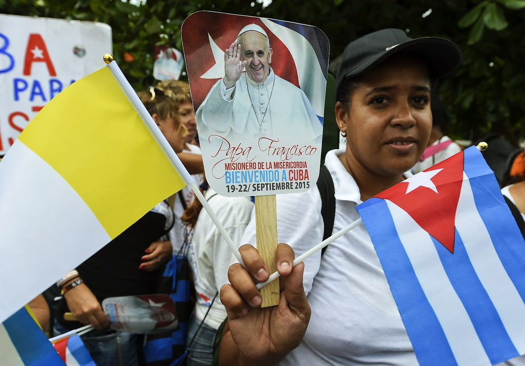 . A woman holds a photo of Pope Francis and Cuban and Vatican flags in Havana during his visit on September 19, 2015. Pope Francis on Saturday urged the United States and Cuba to pursue their nascent reconciliation as he arrived in Havana on the first leg of a high-profile trip that will also take him to the US.       ( LUIS ACOSTA/AFP/Getty Images)