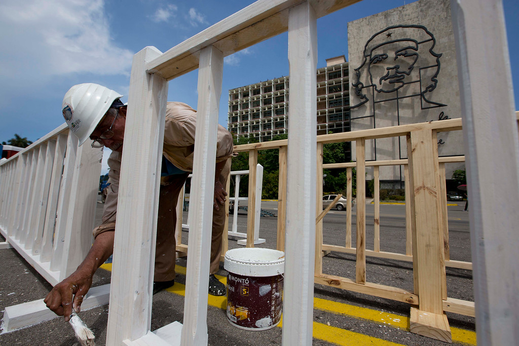 ". Carlo Cabrera paints a fence in Revolution Square, where a sculpture of revolutionary hero Ernesto ""Che\"" Guevara hangs in the background on a government building, in Havana, Cuba, Friday, Sept. 18, 2015, one day before the arrival of Pope Francis. Francis plans to meet with Cuba\'s president and its priests, its young and its sick, its churchgoers and its seminarians as he travels around the island starting Saturday. However, he will not be meeting with dissidents, sparking critiques from the political opposition who say they feel let down by an institution they believe should help push for greater freedom in Cuba. (AP Photo/Alessandra Tarantino)"