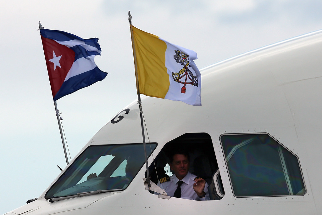 . A pilot gestures from a window as the airplane carrying Pope Francis taxis into position as it arrives at Jose Marti International Airport on September 19, 2015 in Havana, Cuba. Pope Francis is at the beginning of a three day visit to Cuba where he will meet President Raul Castro and hold Mass in Revolution Square before travelling to Holguin, Santiago de Cuba and El Cobre then onwards to the United States.  (Photo by Carl Court/Getty Images)