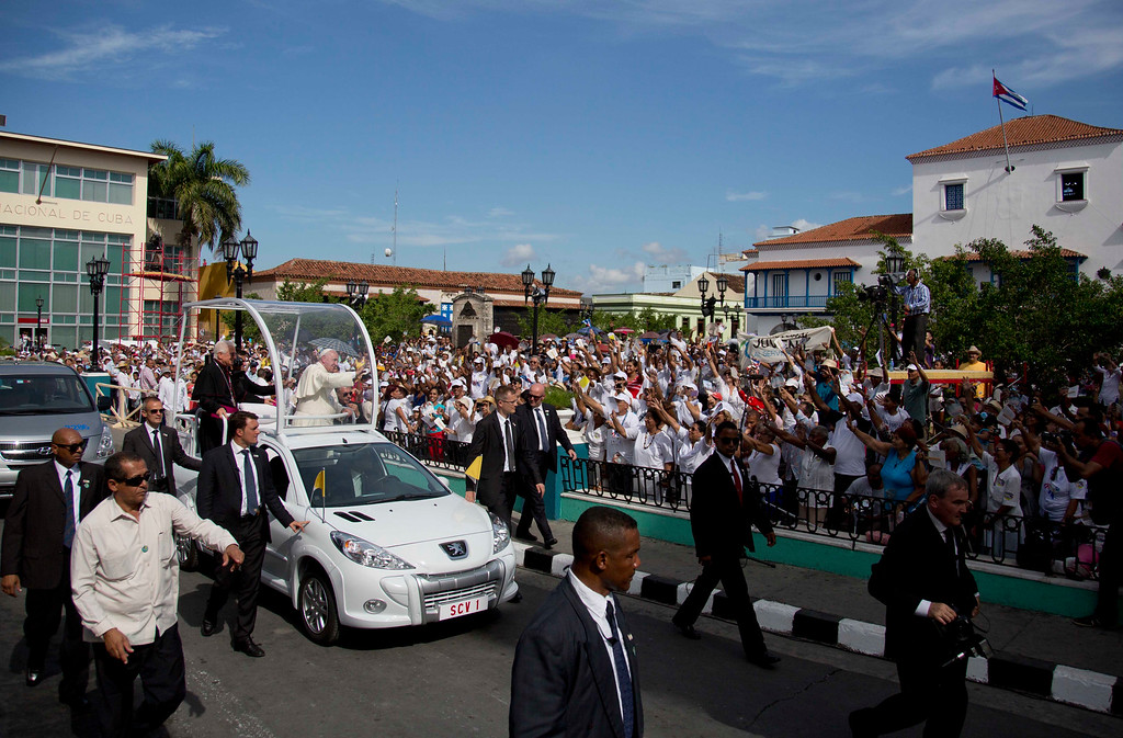 ". Security surrounds Pope Francis\' popemobile as he greets residents as he makes his way to the Metropolitan Cathedral to celebrate Mass in Santiago de Cuba, Cuba, Tuesday, Sept. 22, 2015. Pope Francis on Tuesday called on Cubans to rediscover their Catholic heritage and live a ""revolution of tenderness,\"" powerful words in a country whose 1959 revolution installed an atheist, communist government that sought to replace the church as the guiding force in people\'s lives. (AP Photo/Eduardo Verdugo)"