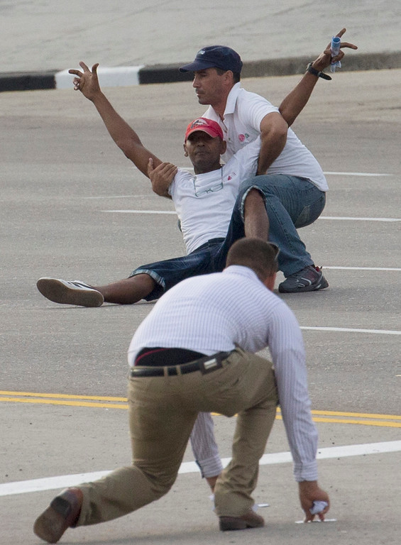 . One of two unidentified men is grabbed by a security officer after as another one collects leaflets they threw as Pope Francis was arriving for a Mass at Revolution Plaza in Havana, Cuba, Sunday Sept. 20, 2015. Francis will not be meeting with dissidents during his visit, sparking critiques from the political opposition who say they feel let down by an institution they believe should help push for greater freedom in Cuba. (AP Photo/Ramon Espinosa)